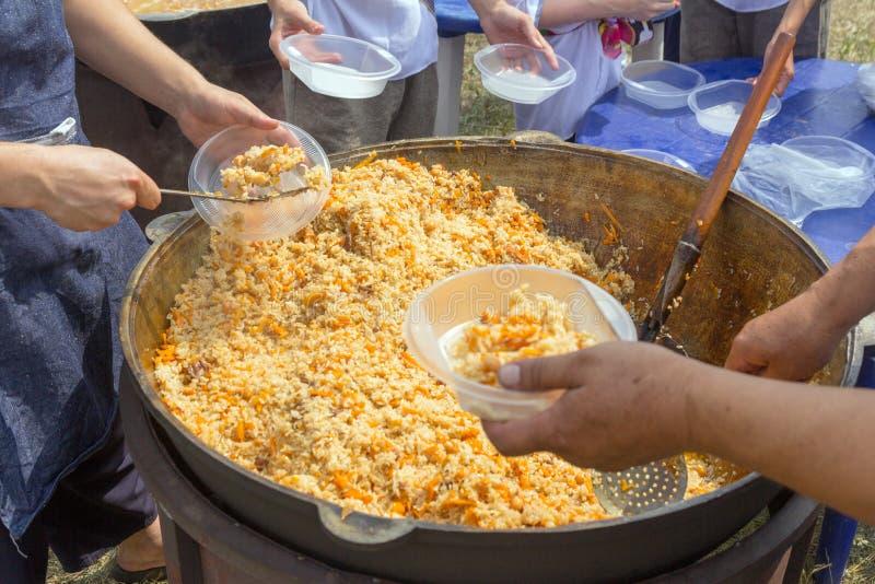 Rusia, Samara, julio de 2018: El cocinero del Uzbek presenta el pilaf cocinado en placas durante el día de fiesta festival Ethno imagenes de archivo