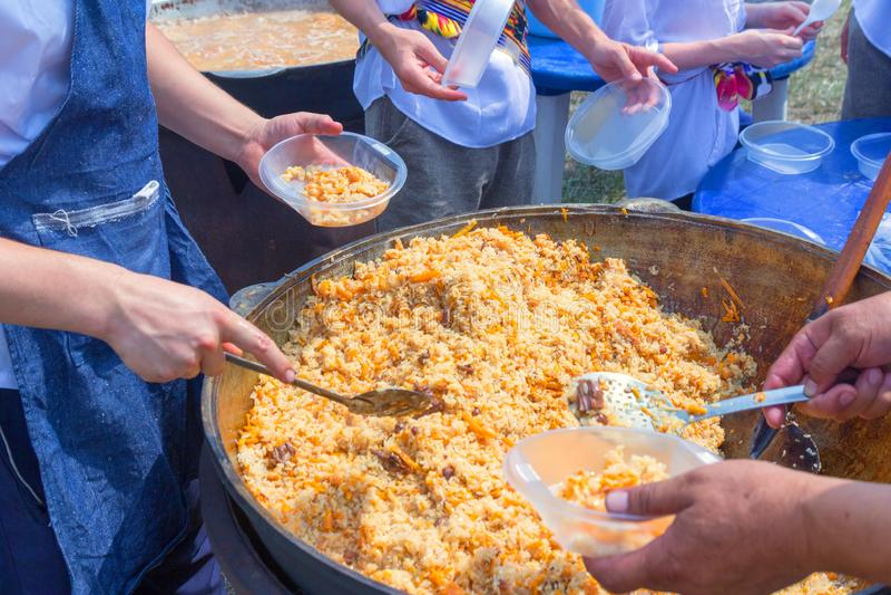 Rusia, Samara, julio de 2018: El cocinero del Uzbek presenta el pilaf cocinado en placas durante el día de fiesta festival Ethno imágenes de archivo libres de regalías