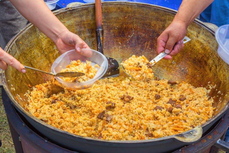 Rusia, Samara, julio de 2018: El cocinero del Uzbek presenta el pilaf cocinado en placas durante el día de fiesta festival Ethno imagen de archivo libre de regalías