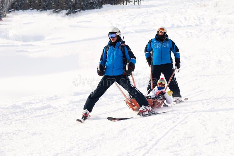 Rusia, Sheregesh 2018 11 17 las salvaciones en los esquís llevan al esquiador que se ha estrellado de árbol, con la pierna vendad fotos de archivo libres de regalías