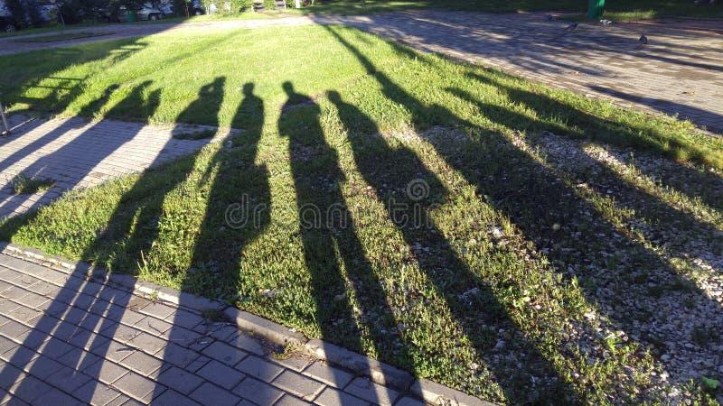 Rusia - sombras de la gente en hierba imagenes de archivo