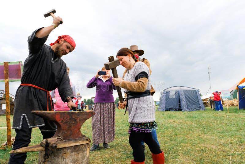 Rusia, Tyumen, 15 06 2019 El herrero lleva a cabo una clase principal en forjar en el festival de diversas naciones Golpee el mar imagen de archivo