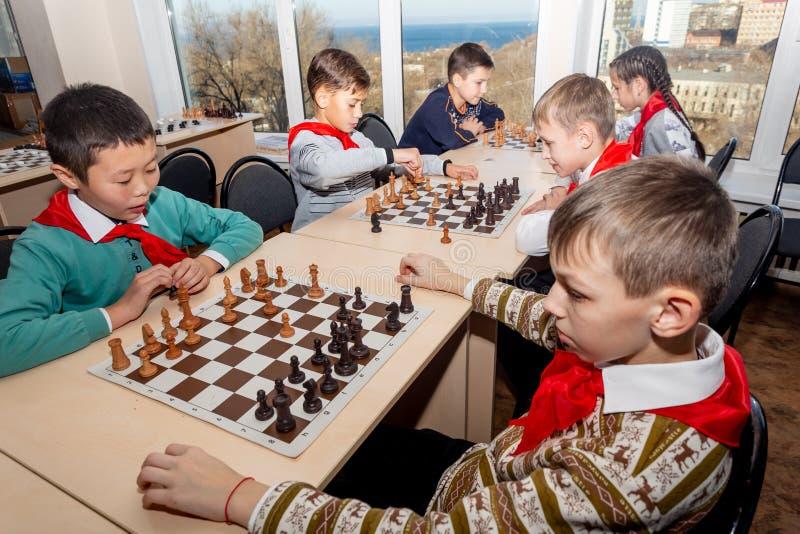 Rusia, Vladivostok, 12/01/2018 Los niños juegan a ajedrez durante la competencia del ajedrez en club de ajedrez Juegos de la educ imágenes de archivo libres de regalías