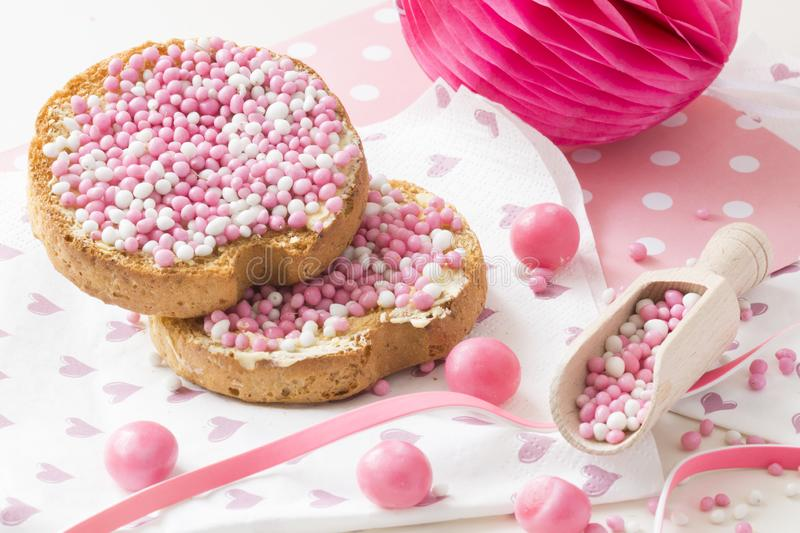 Rusk with pink aniseed balls, muisjes, typical Dutch treat when a baby girl is born in The Netherlands. Rusk with aniseed sprinkles, Dutch muisjes. Tradition in stock photography