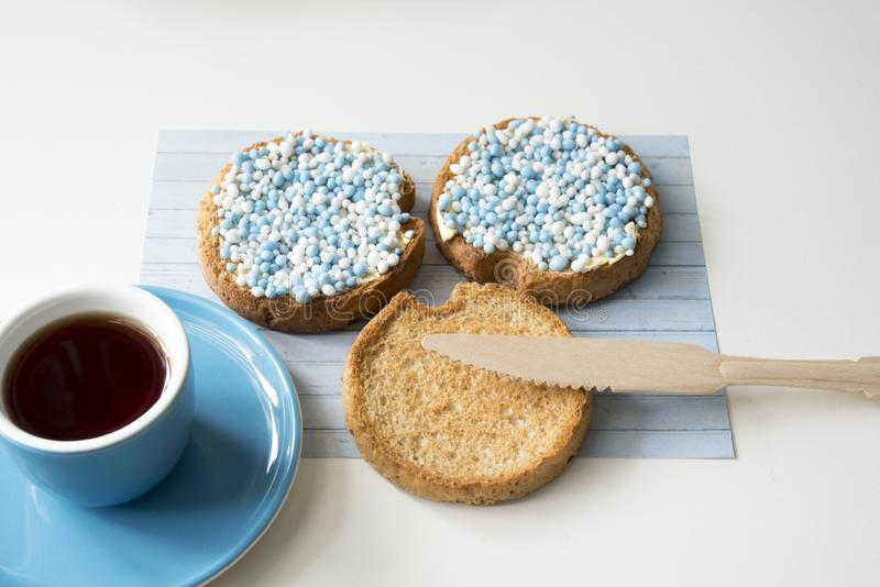 Rusk with blue aniseed balls, muisjes, Dutch treat to celebrate that a baby boy is born in The Netherlands. Cup of coffee and rusk with blue aniseed sprinkles royalty free stock images