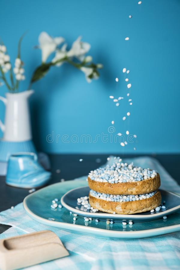 Rusk with blue aniseed balls, muisjes, tradition in the Netherlands to celebrate the birth of a son. Rusk with falling blue aniseed balls, muisjes, on plate royalty free stock photography