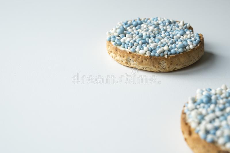 Rusk with blue aniseed balls, muisjes, tradition in the Netherlands to celebrate the birth of a son. space for text. Rusk with blue aniseed balls, muisjes stock photos