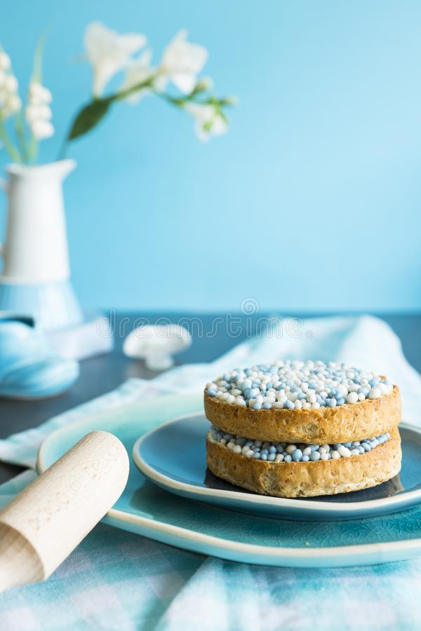 Rusk with blue aniseed balls, muisjes, tradition in the Netherlands to celebrate the birth of a son. Rusk with blue aniseed balls, muisjes, wooden spoon and royalty free stock photography