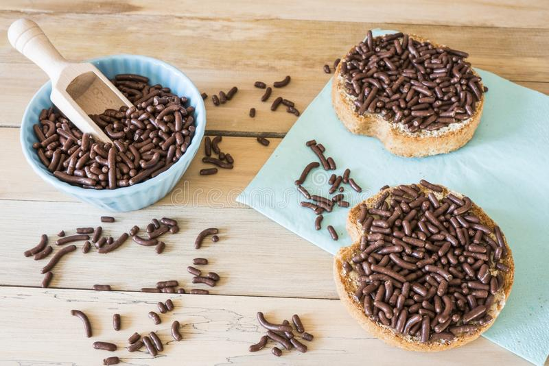 Rusk with chocolate sprinkles, Dutch Hagelslag, on wooden table stock photos