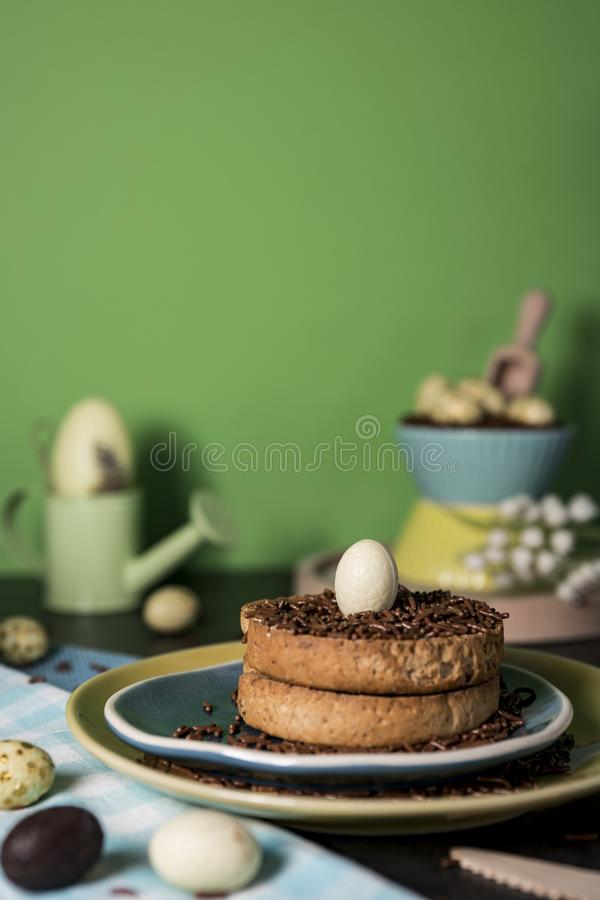 Rusk with Dutch chocolate hail and chocolate Easter eggs. Easter morning scene with rusk and chocolate hail hagelslag, and chocolate eggs. against green stock images
