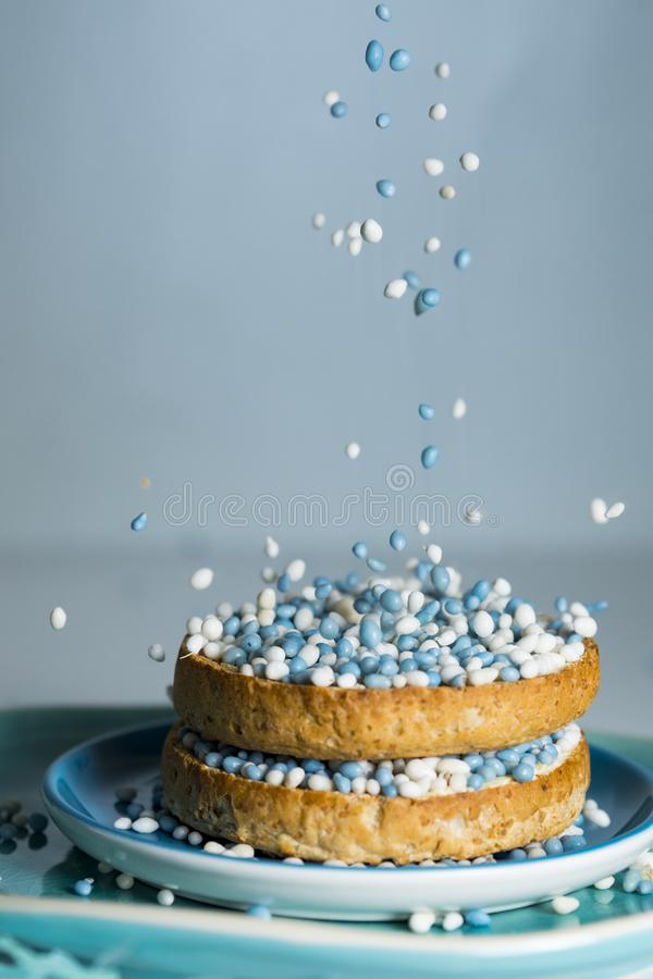 rusk with falling blue aniseed balls, muisjes, tradition in the Netherlands to celebrate the birth of a son stock photo