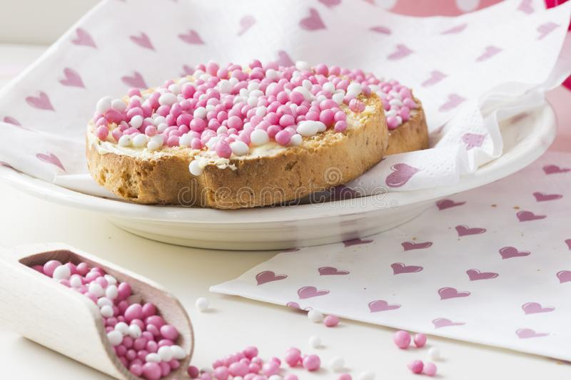 Rusk with pink aniseed balls, muisjes, typical Dutch treat when a baby girl is born in The Netherlands. Close up rusk with white pink aniseed sprinkles, Dutch royalty free stock photos