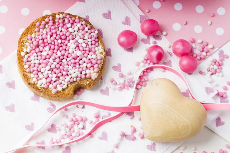 Rusk with pink aniseed balls, muisjes, typical Dutch treat when a baby girl is born in The Netherlands. Pink flat lay: rusk with aniseed sprinkles, Dutch muisjes royalty free stock image