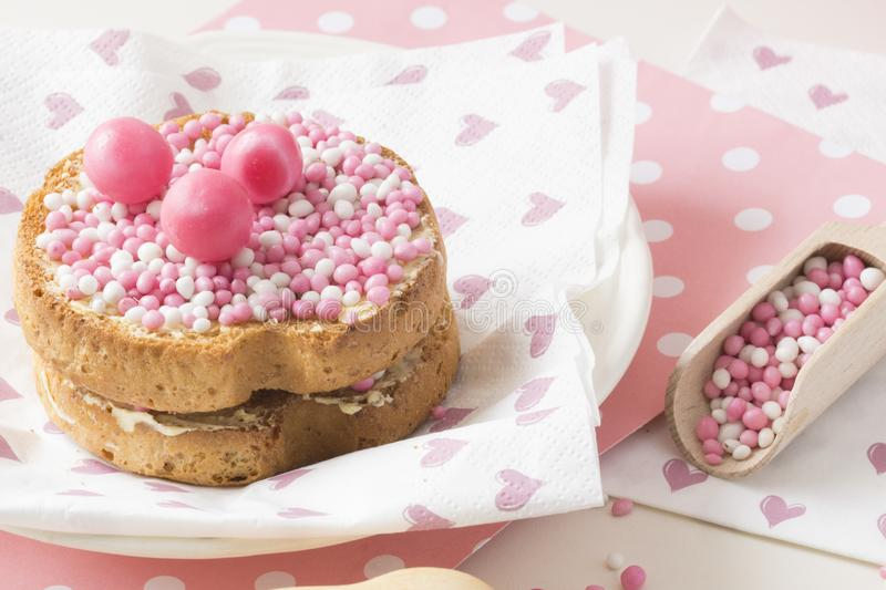 Rusk with pink aniseed balls, muisjes, typical Dutch treat when a baby girl is born in The Netherlands. Rusk with pink aniseed sprinkles, Dutch muisjes stock image
