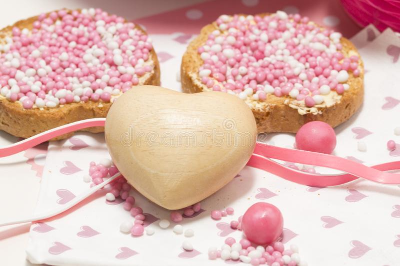 Rusk with pink aniseed balls, muisjes, typical Dutch treat when a baby girl is born in The Netherlands. Rusk with pink white aniseed sprinkles. Dutch muisjes stock photo