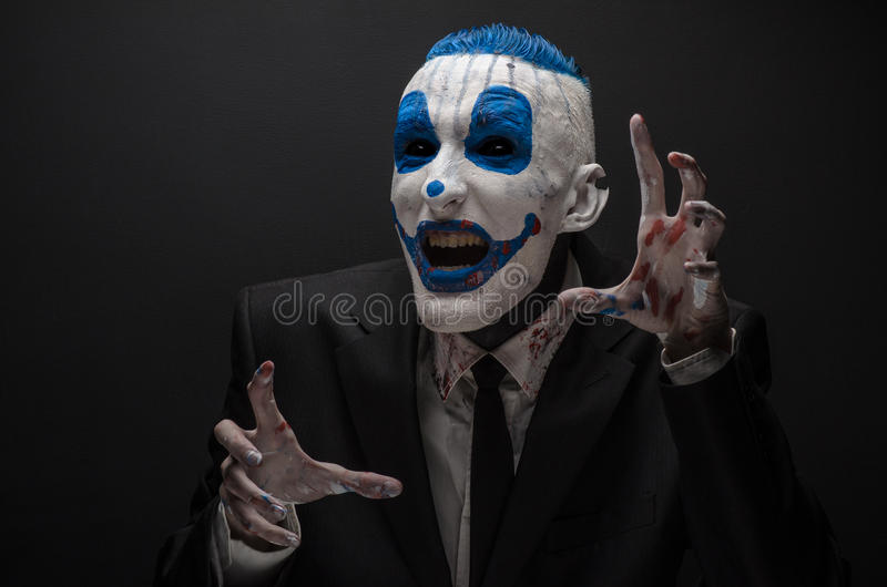 Ruskig clown och allhelgonaaftontema: Galen blåttclown i den svarta dräkten som isoleras på en mörk bakgrund i studion royaltyfri bild