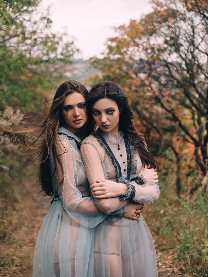 Ruskig dam två i långa vita klänningar som kramar sig royaltyfri foto