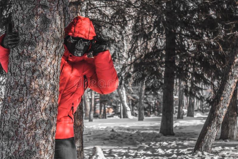 Ruskig maskerad man som väntar på ett offer i skogen royaltyfria bilder
