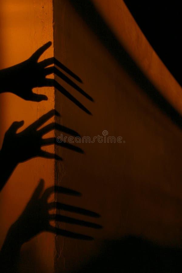 Ruskiga skuggor abstrakt bakgrund Svartskuggor av stora händer på väggen royaltyfria foton