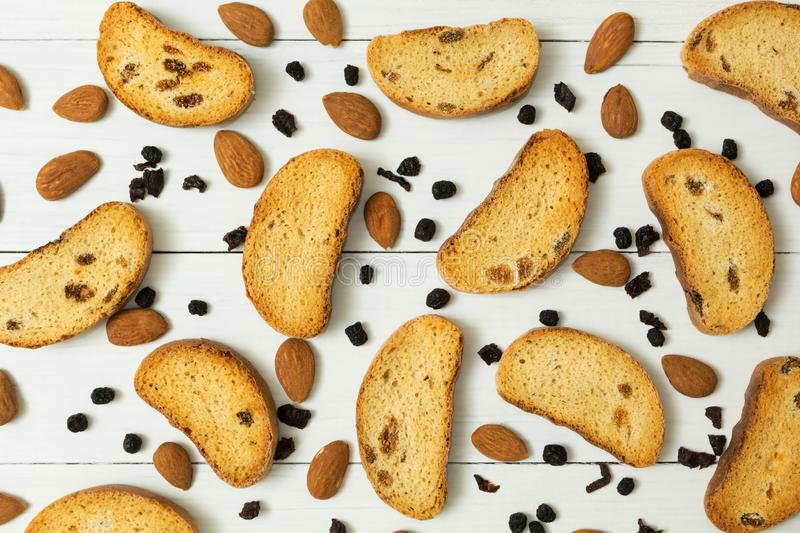 Rusks with raisins, almonds and dried berries on a white wooden background, diet food royalty free stock photography