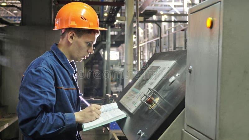 RUSLAND, ANGARSK - 8 JUNI, 2018: De exploitant controleert controlebord van productielijn Vervaardiging van plastic waterpijpen stock foto's