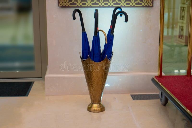 Rusland, Bolgar - Juni 09, 2019 Kol Gali Resort Spa: Blauwe paraplu's in een gouden mand bij de ingang aan een luxehotel royalty-vrije stock foto's