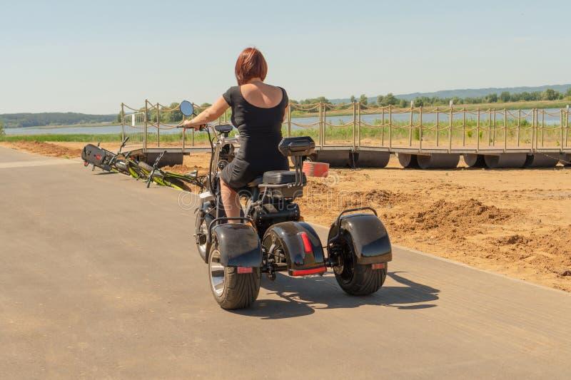 Rusland, Bolgar - Juni 08, 2019 Kol Gali Resort Spa: Een jong meisje in een zwarte kleding met rood haar die haar three-wheeled e stock foto