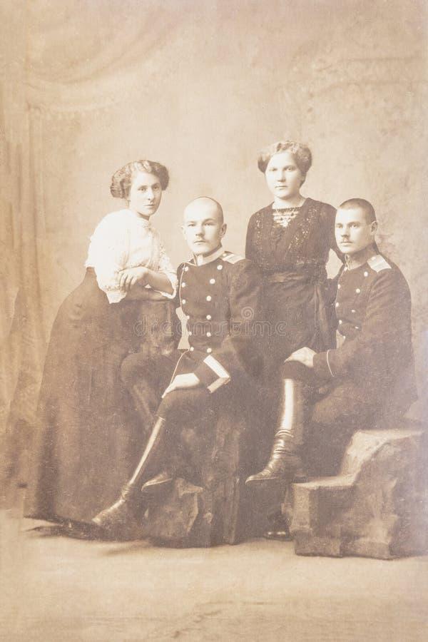 RUSLAND - CIRCA 1905-1910: Een antieke foto toont twee militairen met meisjes die voor camera stellen stock fotografie