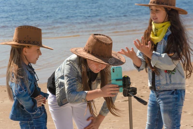 Rusland, Kazan - Mei 25, 2019: Drie tienermeisjes nemen een selfie op iPhone Xs op een zonnige dag stock fotografie