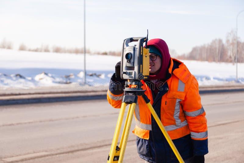 Rusland Kemerovo 2019-03-15 Land en bouwlandmetersmateriaal Geodesist controleert robotachtige totale posttheodoliet royalty-vrije stock afbeelding
