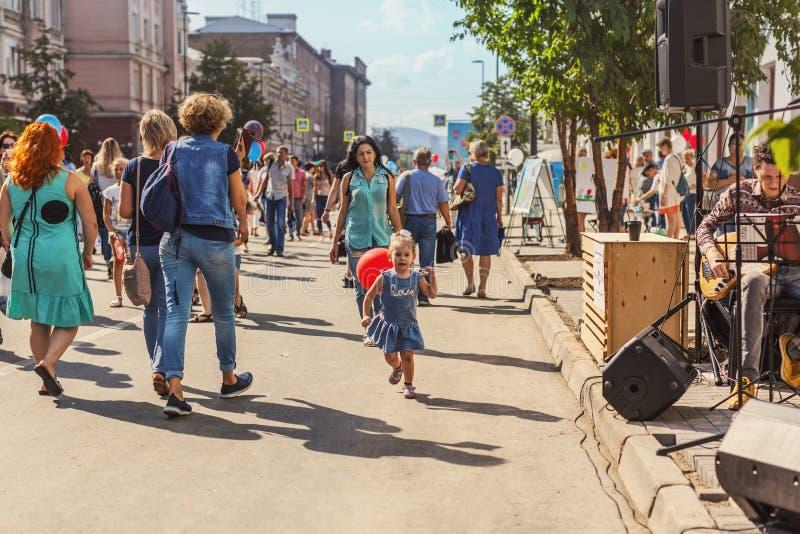 RUSLAND, Krasnoyarsk - Augustus 25: Een klein meisje met een rode ballonlooppas onder mensen langs Prospekt Mira op de dag van de royalty-vrije stock foto