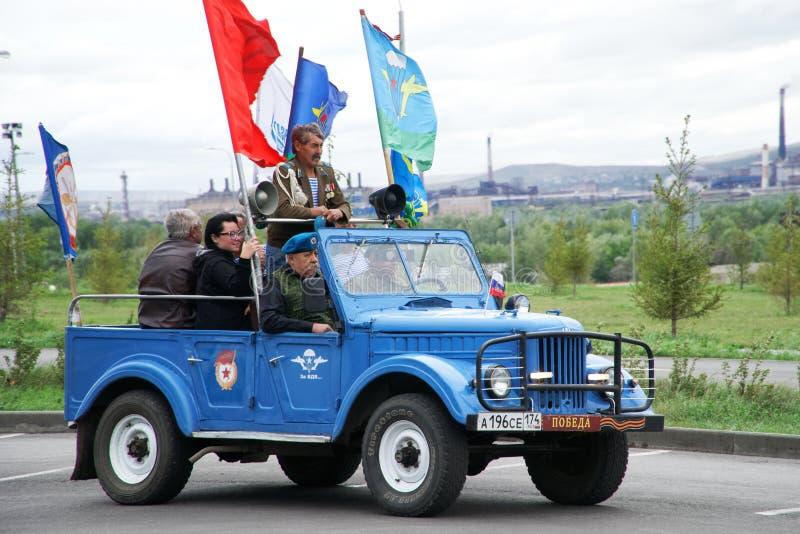 Rusland, Magnitogorsk, 2 Augustus, 2019 Een groep valschermjagers reist rond de stad in oude Russische convertibel tijdens royalty-vrije stock afbeelding
