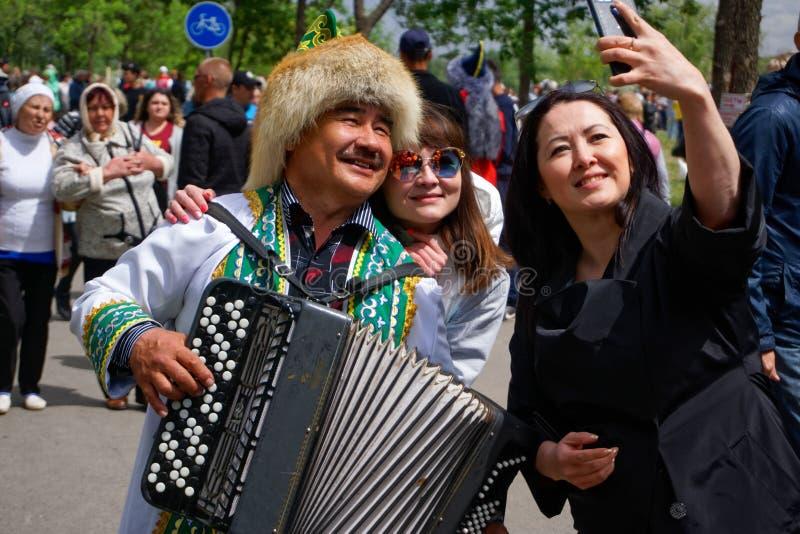 Rusland, Magnitogorsk, - 15 Juni, 2019 De meisjes nemen een selfie met een harmonika in volkskostuum tijdens Sabantuy - de ingeze royalty-vrije stock afbeelding