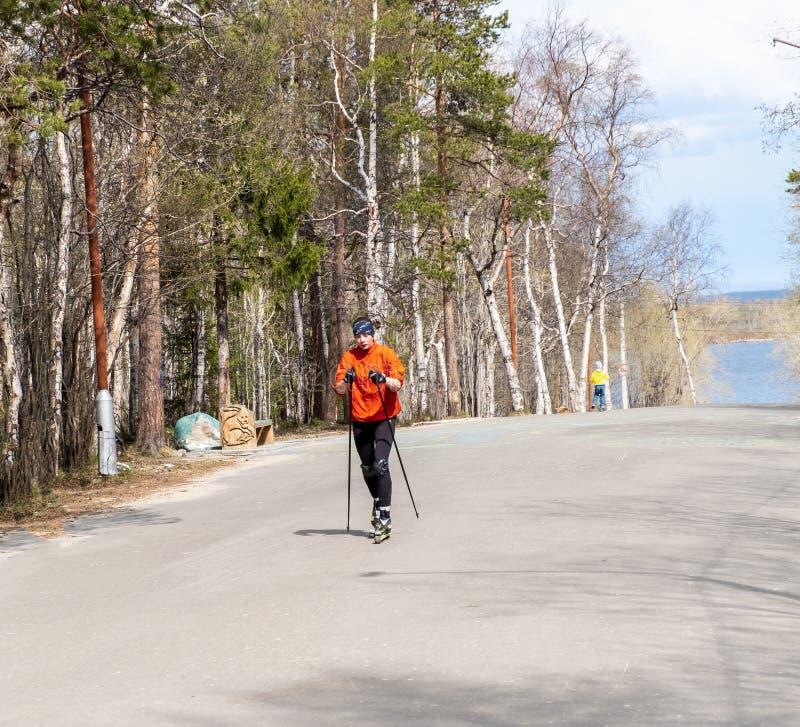 Rusland Monchegorsk - Mei 2019 De opleiding van een atleet op de rolschaatsers Biathlonrit op de rolskis met skistokken, in royalty-vrije stock foto's