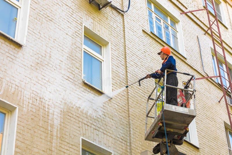 22 05 2019 Rusland, Moskou De werknemer van de gemeentelijke diensten wast een voorgevel van het gebouw met meerdere verdiepingen stock fotografie
