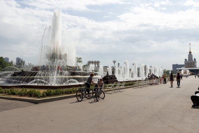 Rusland, Moskou, Mensen met fietsen die bij de fontein rusten stock afbeelding