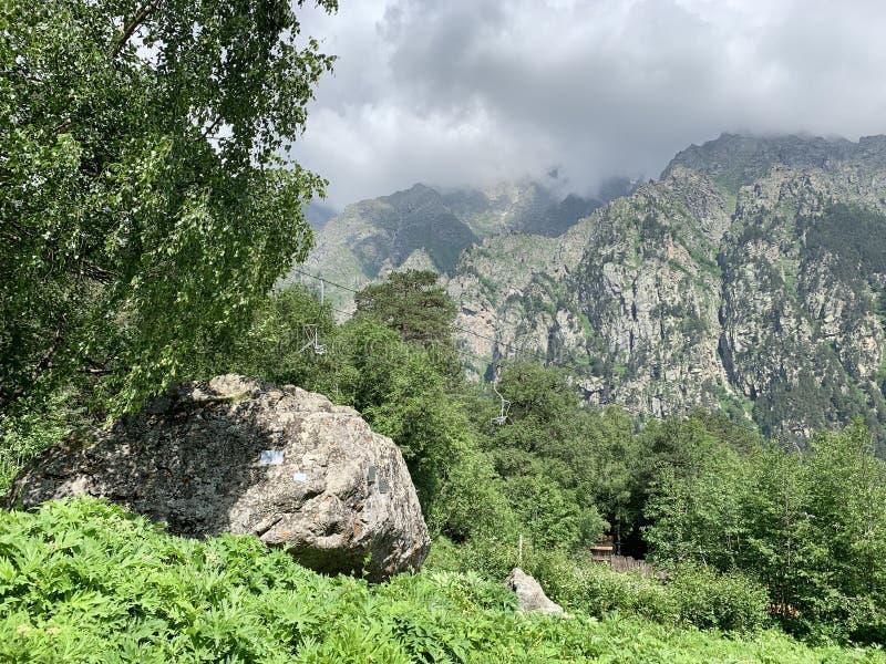 Rusland, Noord-Osseti? Tseykloof, herdenkingssteen dichtbij de weg aan de gletsjer 'sprookje 'in de zomer royalty-vrije stock fotografie