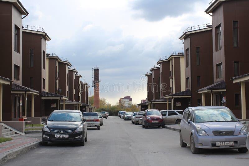 Rusland, Novosibirsk, Novomarusino 27 September, 2015: geparkeerde auto's in een woonwijk dichtbij laag-stijgingsgebouwen royalty-vrije stock foto