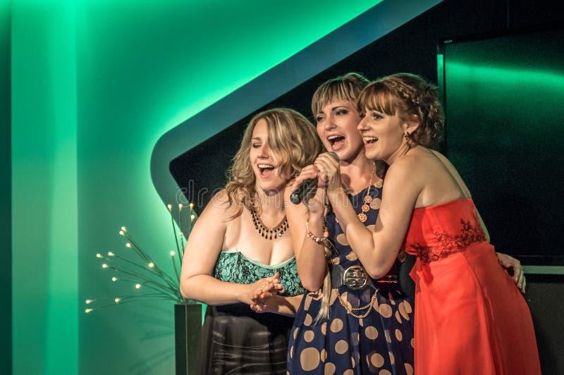 Rusland, Ryazan - 30 06 2014: drie Mooie meisjes die zich met microfoon bevinden die passionately met gesloten ogen zingen stock afbeeldingen