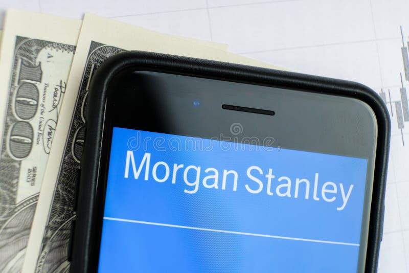RUSLAND, ST PETERSBURG, 4 April, 2019: Logo Morgan Stanley in de smartphone het liggen grafieken en de dollarrekeningen stock foto's