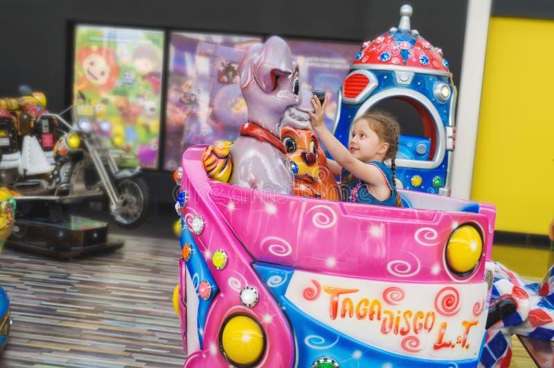 Rusland, St. Petersburg, 06/22/2019 Meisjeritten op de carrousel van de kinderen in hypermarket royalty-vrije stock fotografie