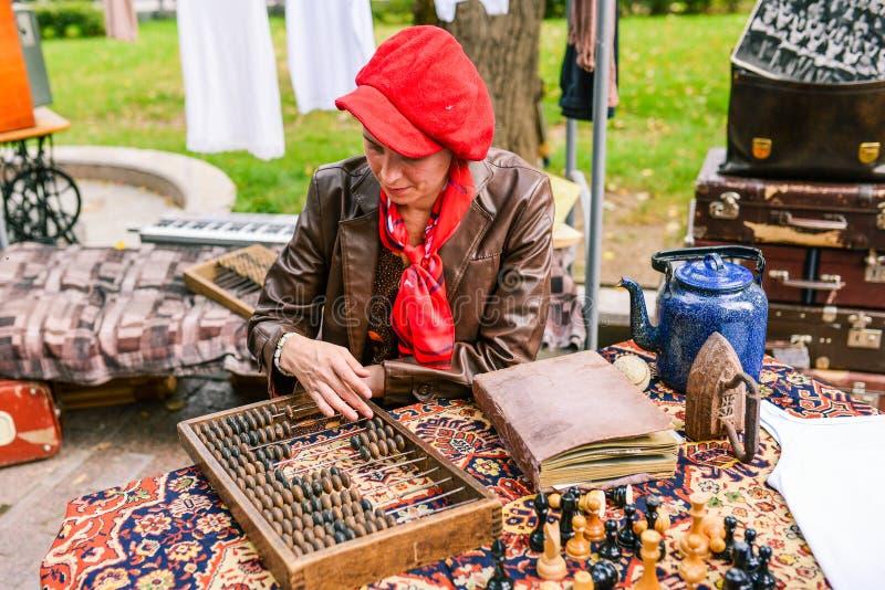 Rusland, stad Moskou - September 6, 2014: Een vrouw met een leerjasje en een rode barettellingen op een tellende raad Tellende ra stock fotografie