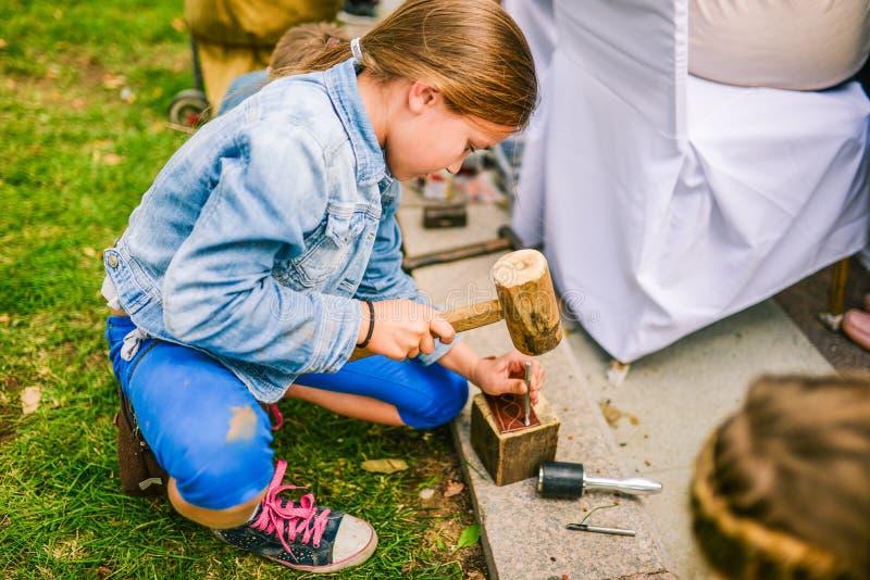 Rusland, stad Moskou - September 6, 2014: Meisje het bonzen met een houten hamer Productie, vervaardiging van leergoederen E stock foto's