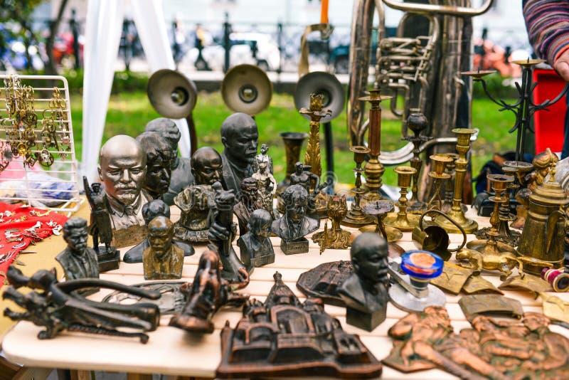 Rusland, stad Moskou - September 6, 2014: Sovjetbeeldjes van leiders en kunstenaars Tribunes voor kaarsen Verkopende antiquair in stock foto's