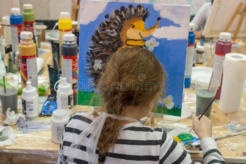 Rusland, Tatarstan, 20 April, 2019 Het meisje trekt een egel Creatief tienermeisje die een beeld op schildersezel paitning Binnen stock foto