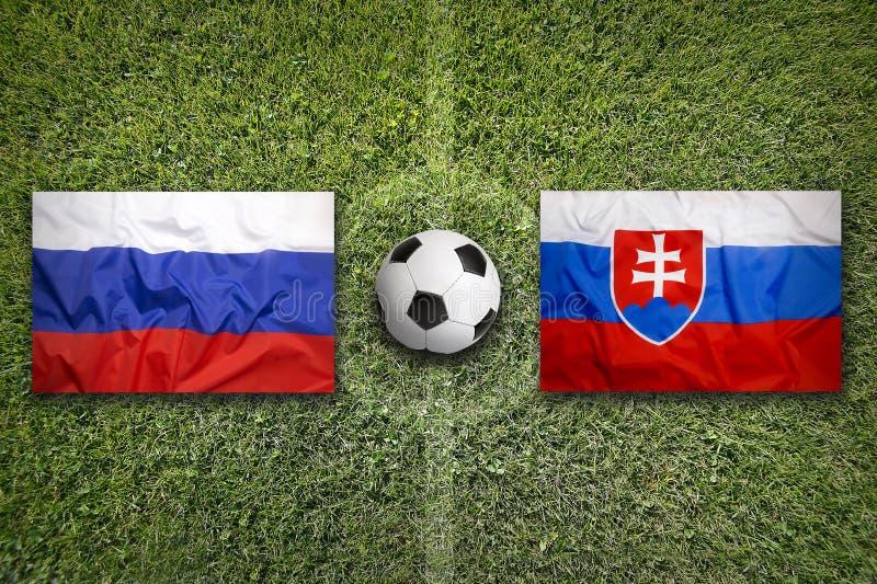 Rusland versus De vlaggen van Slowakije op voetbalgebied stock fotografie