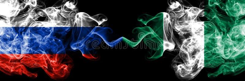 Russe contre le Nigéria, drapeaux nigériens de fumée placés côte à côte Drapeaux soyeux colorés épais de fumée de la Russie et du photographie stock libre de droits