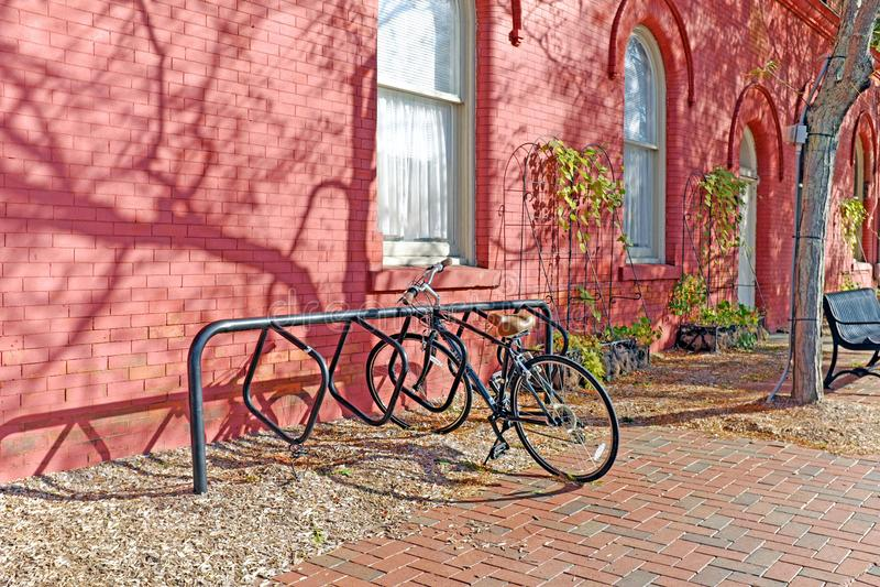 Russet orange brick sidewalk, red pear painted building, and bike make an autumn scene stock photo