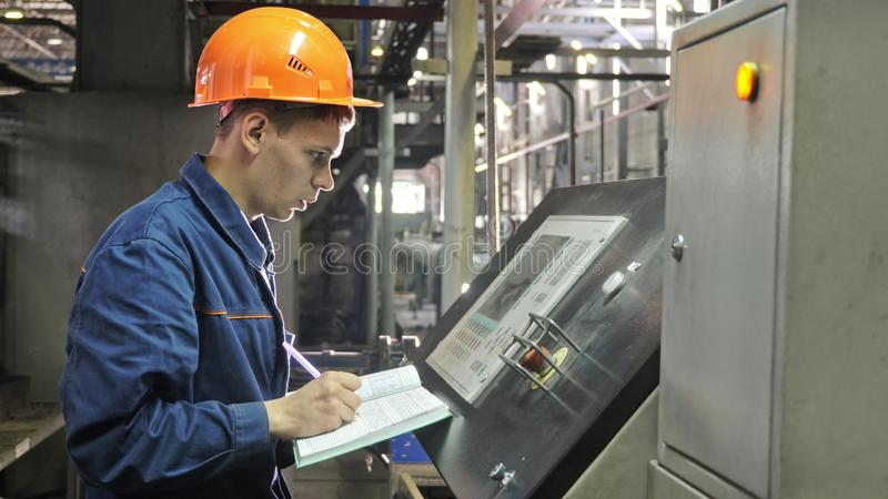 RUSSIA, ANGARSK - JUNE 8, 2018: Operator monitors control panel of production line. Manufacture of plastic water pipes stock photos