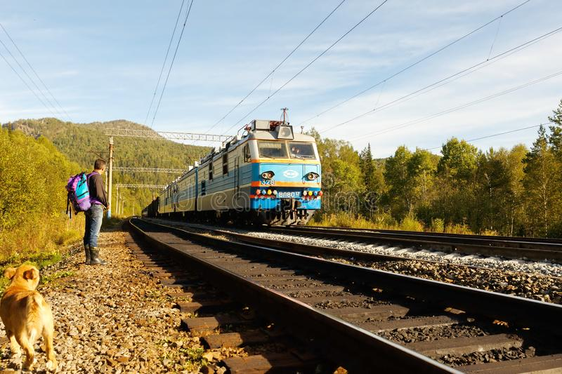 A tourist with a backpack stands near the railway in the Ural Mountains. Russia, Bashkortostan, September 2016: A tourist with a backpack stands near the stock photos